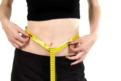 Valokuvassa nainen mittaa vyötärön ympärystä.