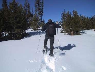 Valokuvassa lumikenkäilijä talvisessa maisemassa.