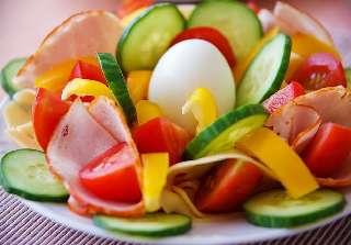 Valokuvassa kurkkua, tomaattia, paprikaa ja kananmuna.
